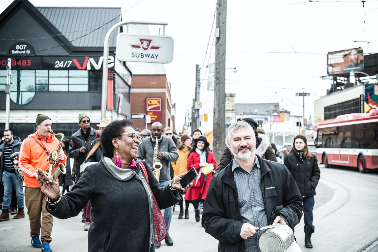 A man and a woman lead a parade down a busy street.
