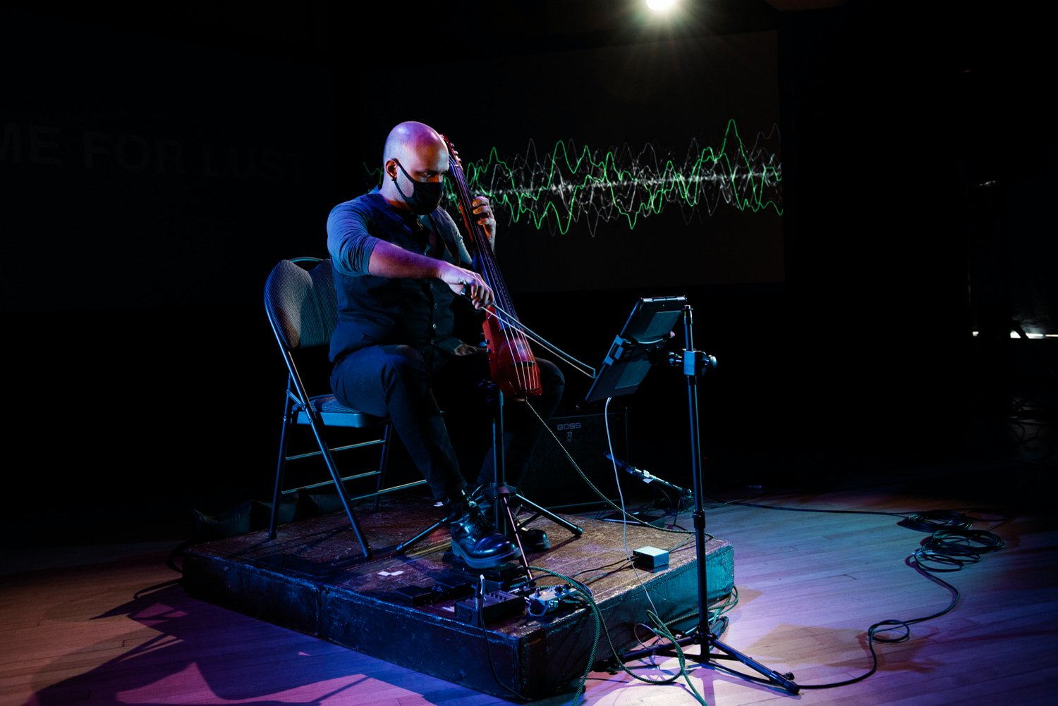 A musician plays an electric cello while seated in front of a projected representation of an audio wave.