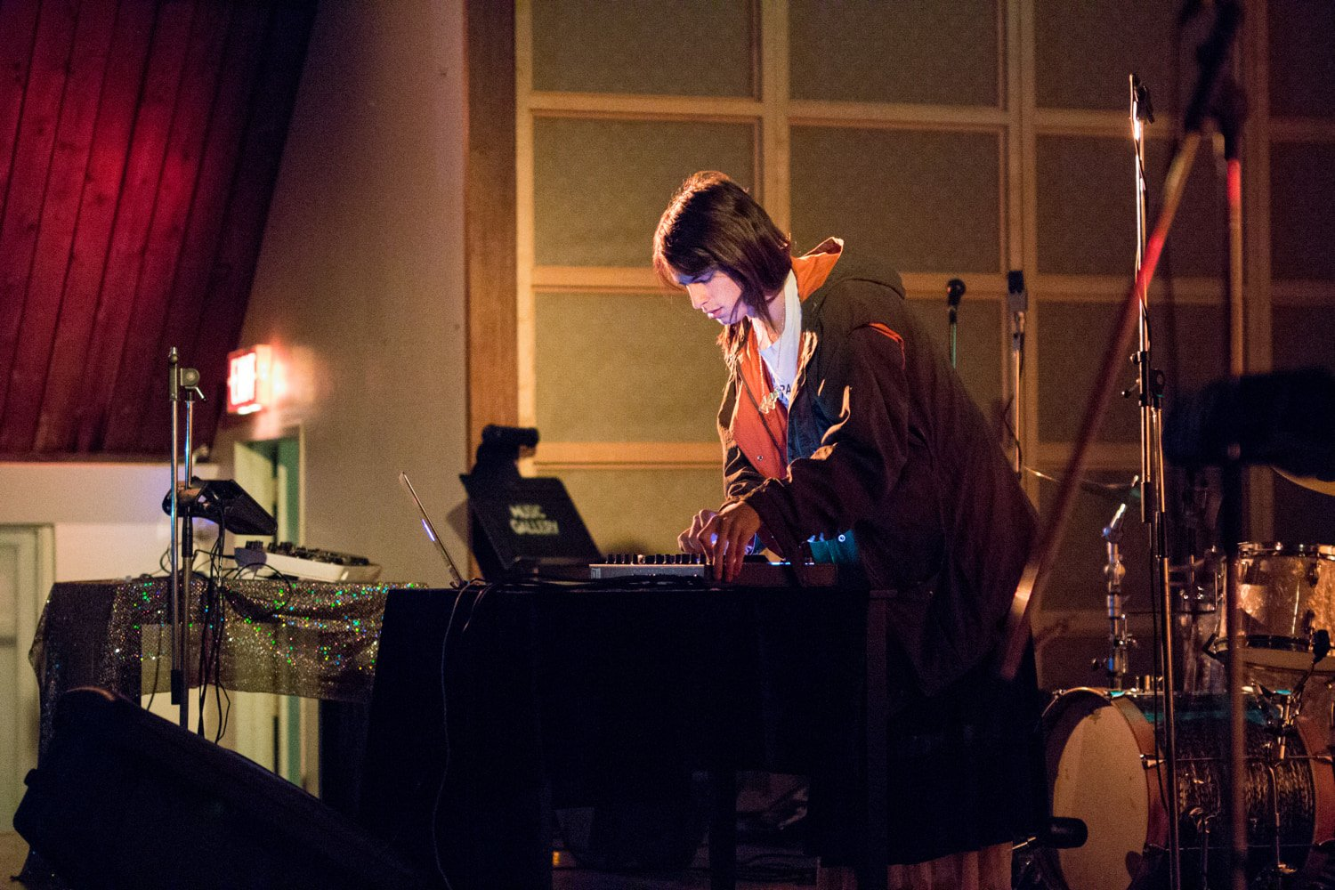 A musician works with a laptop and electronics while standing on stage.