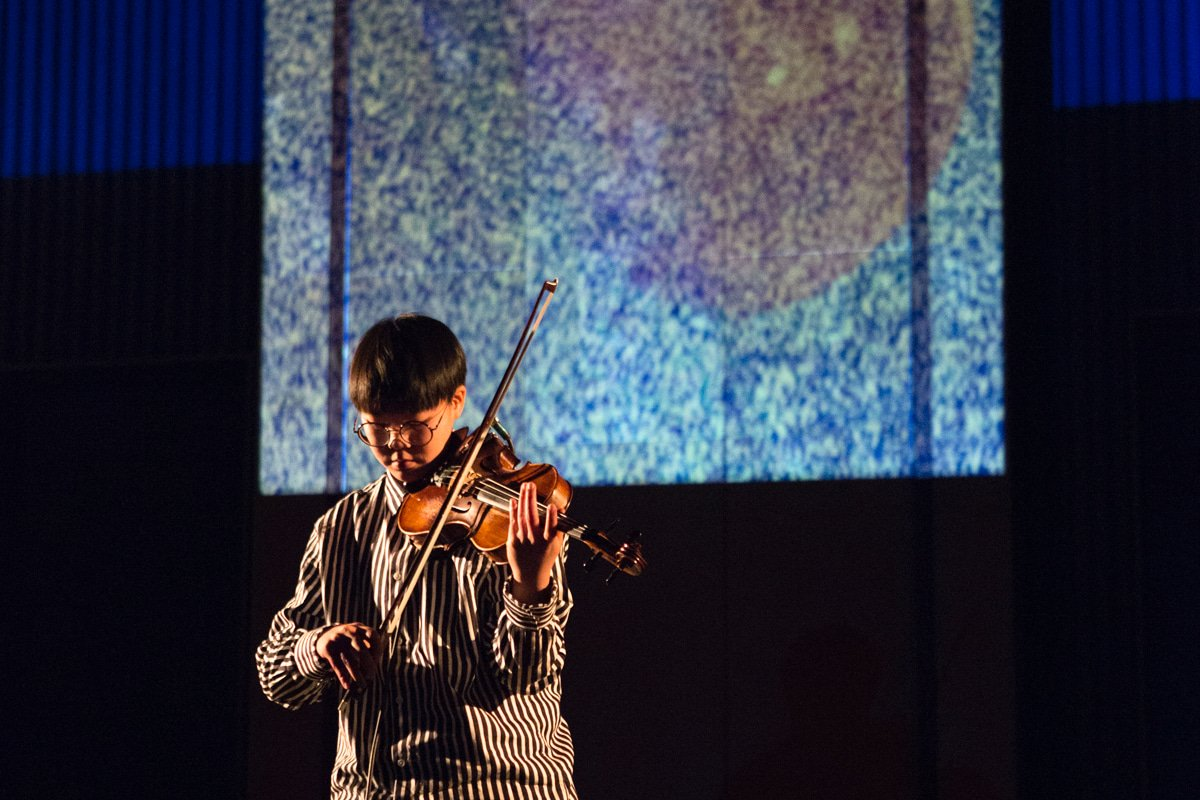 A violinist performs in front of projected images