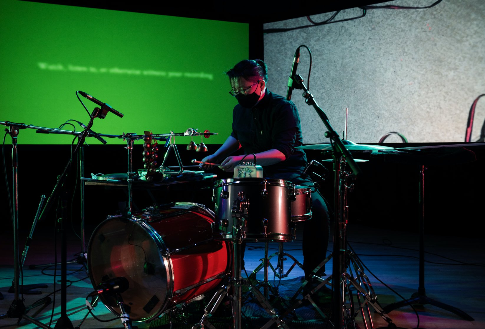 A drummer performs in front of two projection screens.