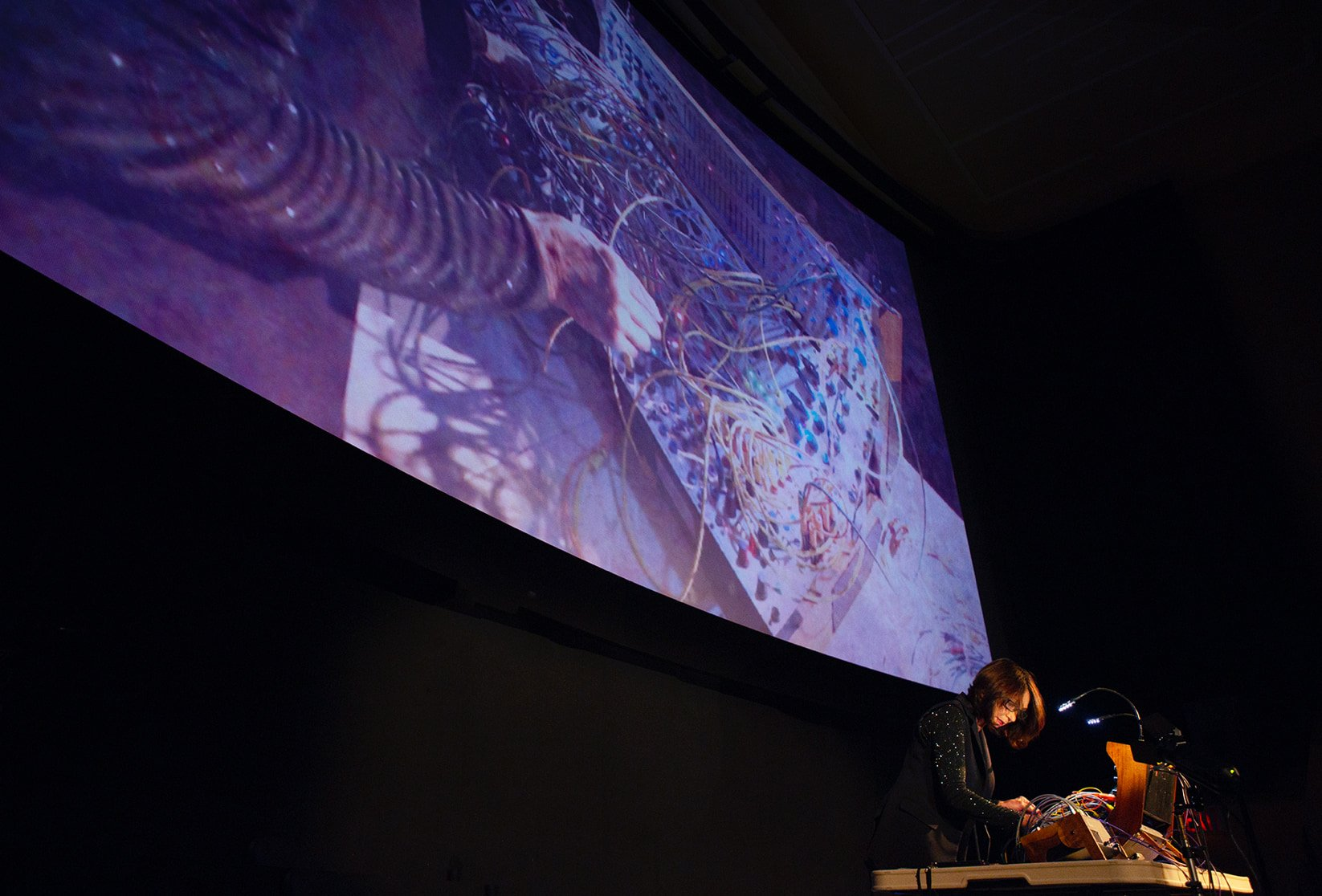 An instrumentalist plays a synthesizer; her instrument is projected on a wide screen behind her.