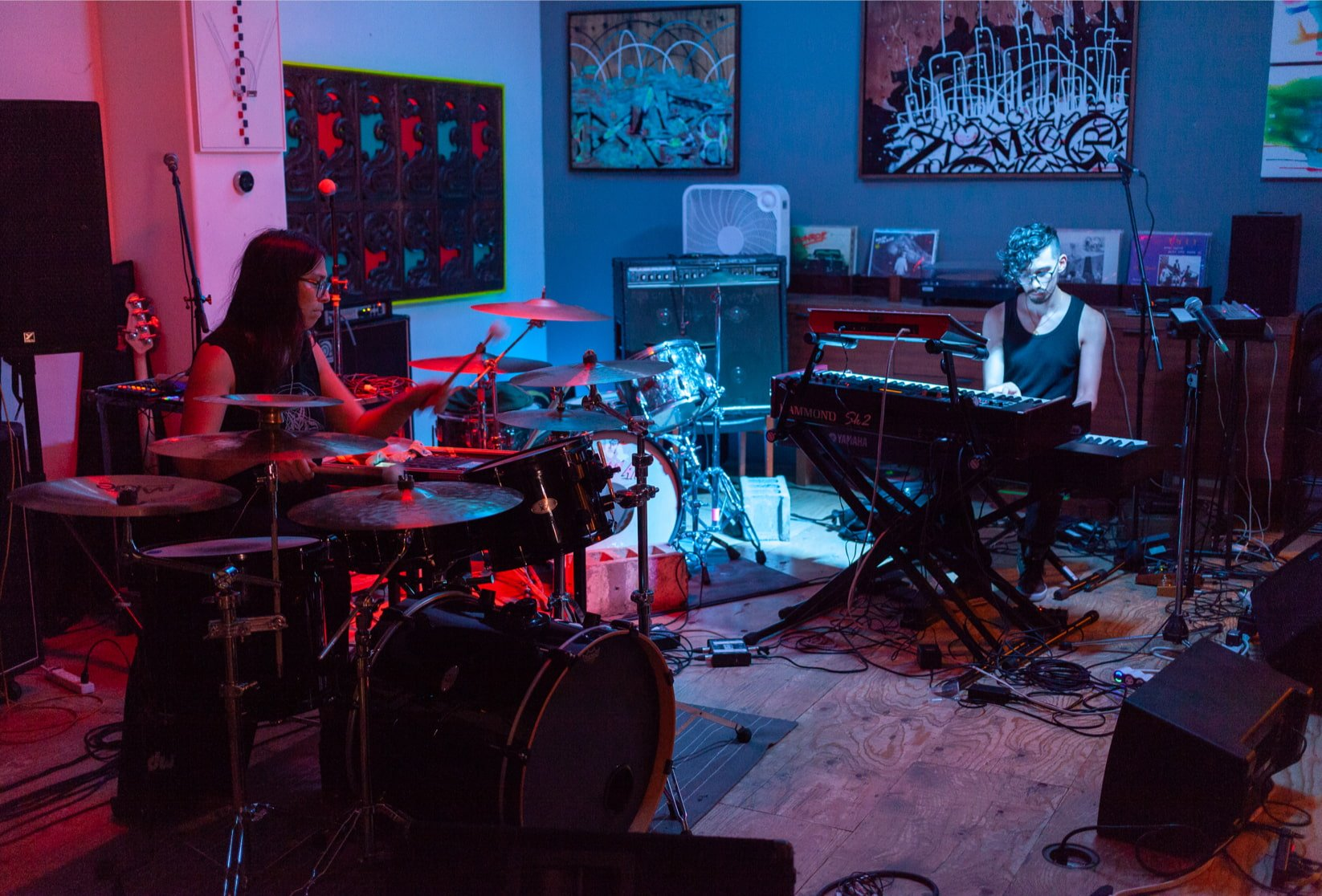A drummer and a keyboardist in performance in a small room with many paintings.