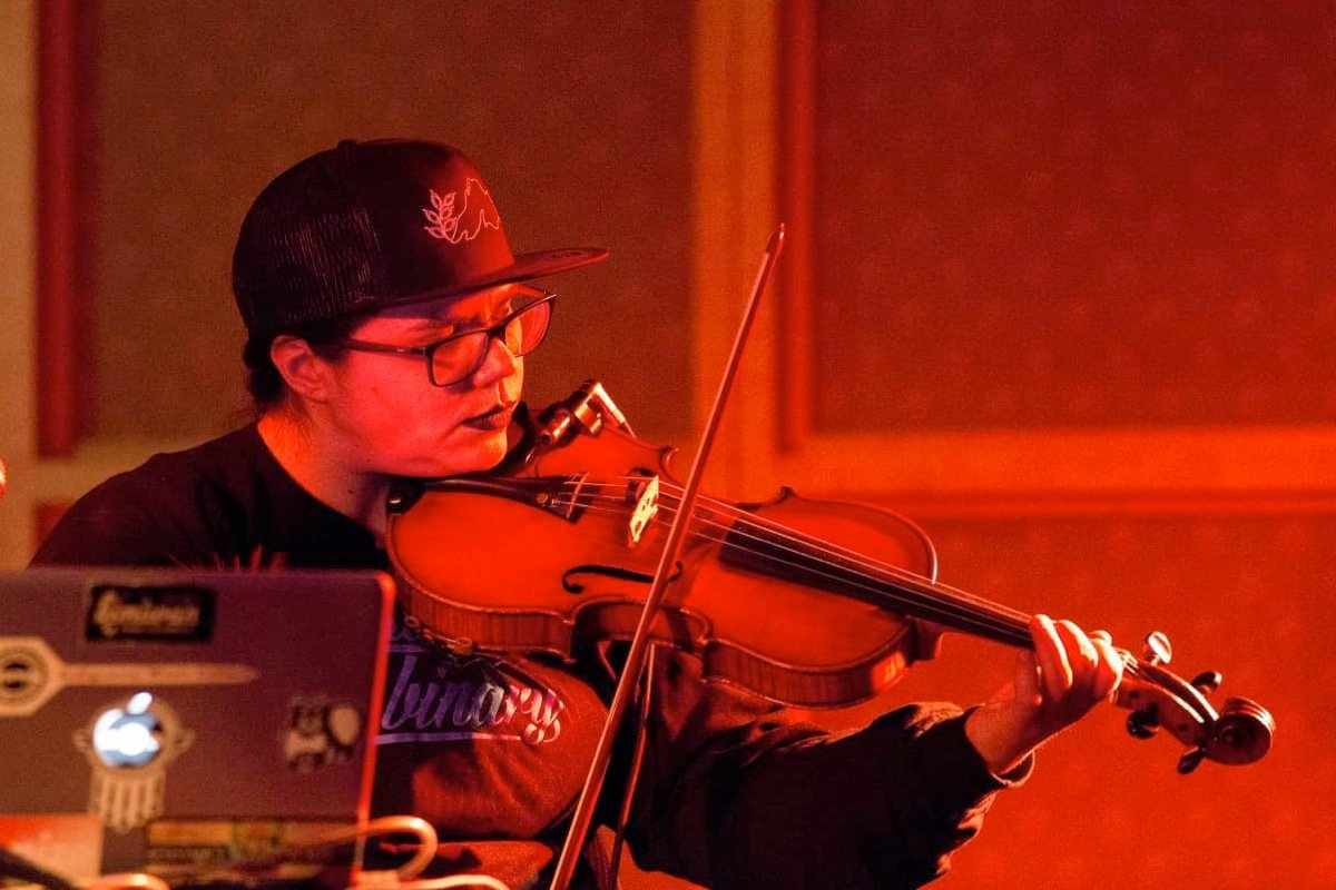 A violist performs seated in front of a laptop